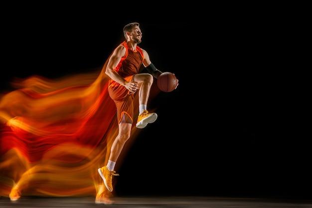 Die feuerspuren. junger kaukasischer basketballspieler der roten mannschaft in aktion