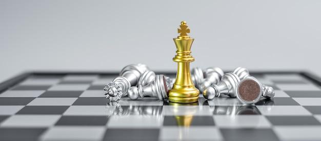 Die figur des gold chess king hebt sich während des schachbrettwettbewerbs von der masse der gegner oder gegner ab.