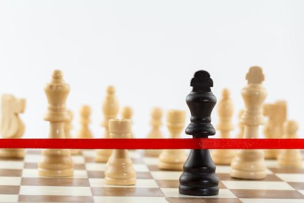 Die figur des königs überquert das rote abschlussband. schachgeschäftsführung und erfolgskonzept