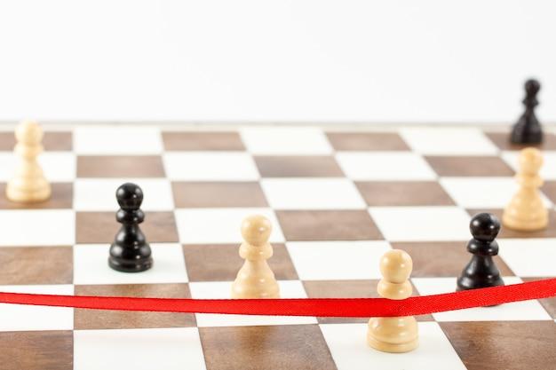Die figur des weißen bauern überquert das rote zielband. schachführungs- und erfolgskonzept