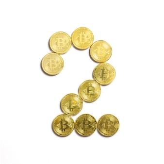 Die figur von 2 aus bitcoin-münzen ausgelegt und auf weißem hintergrund isoliert