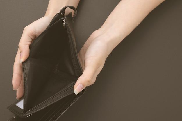 Die finanzkrise aufgrund der coronavirus-pandemie. leere brieftasche ohne geld in weiblichen händen