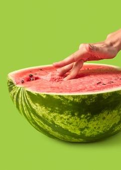 Die finger der frau berühren das püree der reifen frischen wassermelone aus biologischem anbau