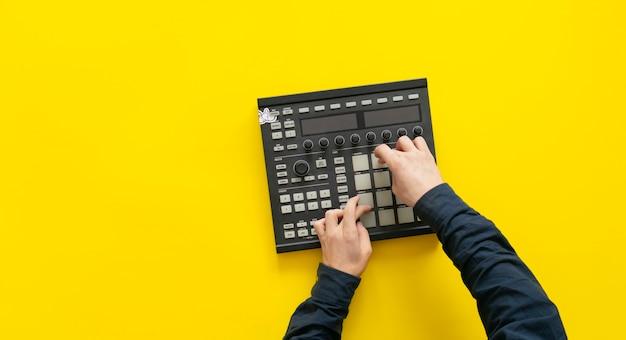 Die finger des dj-audioproduzenten spielen die drum-musik auf den pads der drum-machine