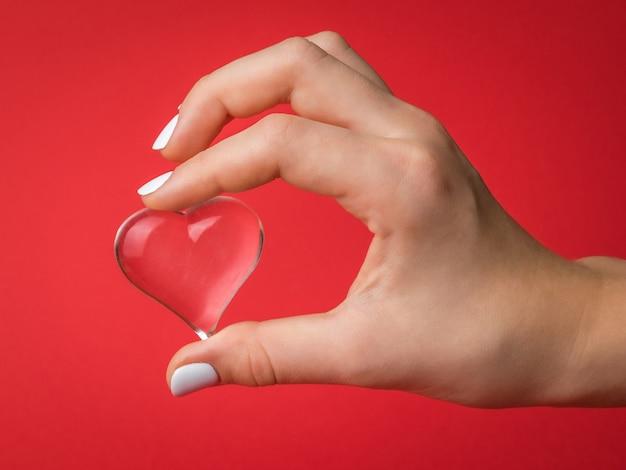 Die finger des kindes halten sanft ein glasherz auf rotem grund. ein symbol für liebe und leben.