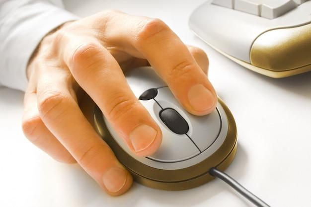 Die finger klicken auf eine computermaus in der nähe eines teils der tastatur