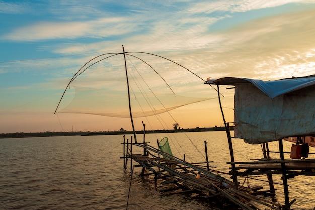 Die fischen-werkzeuge des fischers im see am sonnenunterganghimmel.