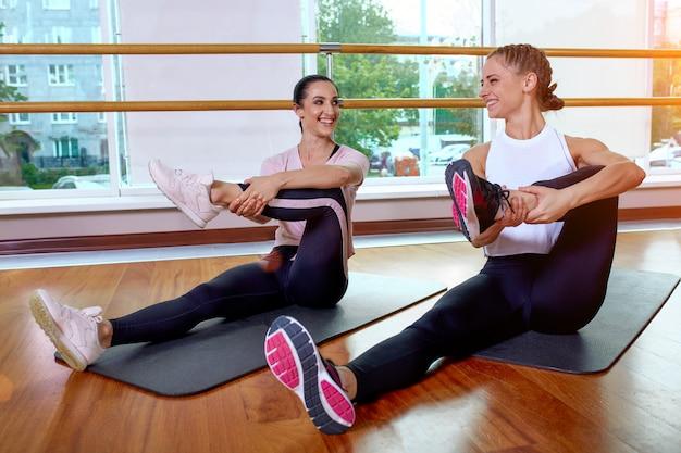 Die fitnessgruppe macht übungen zum dehnen der muskeln in einer fitnessstunde.
