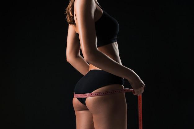 Die fitte frau, die perfekte form einer schönen figur misst. gesunder lebensstil und fitnesskonzept