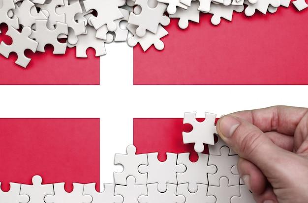 Die flagge dänemarks ist auf einem tisch abgebildet, auf dem die menschliche hand ein puzzle weißer farbe faltet