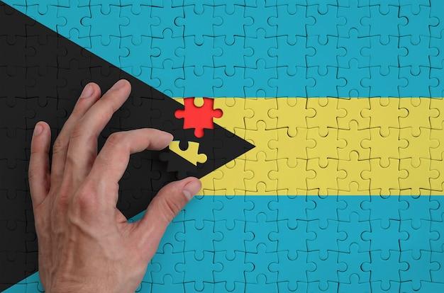 Die flagge der bahamas ist auf einem puzzle abgebildet, das mit der hand des mannes gefaltet wird