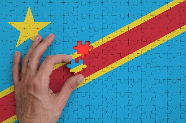 Die flagge der demokratischen republik kongo ist auf einem puzzle abgebildet, das mit der hand des mannes gefaltet wird
