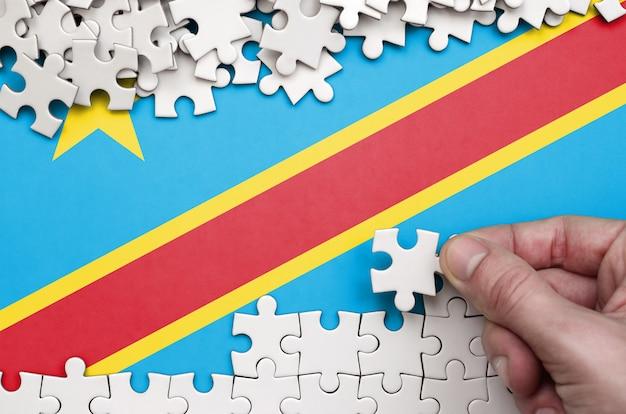 Die flagge der demokratischen republik kongo ist auf einem tisch abgebildet, auf dem die menschliche hand ein puzzle weißer farbe faltet