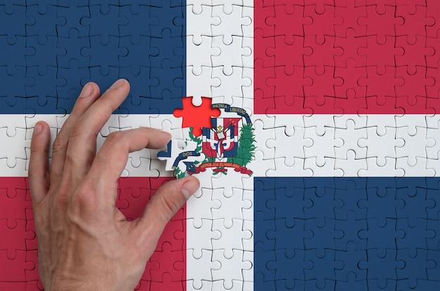 Die flagge der dominikanischen republik ist auf einem puzzle abgebildet, das mit der hand des mannes gefaltet wird