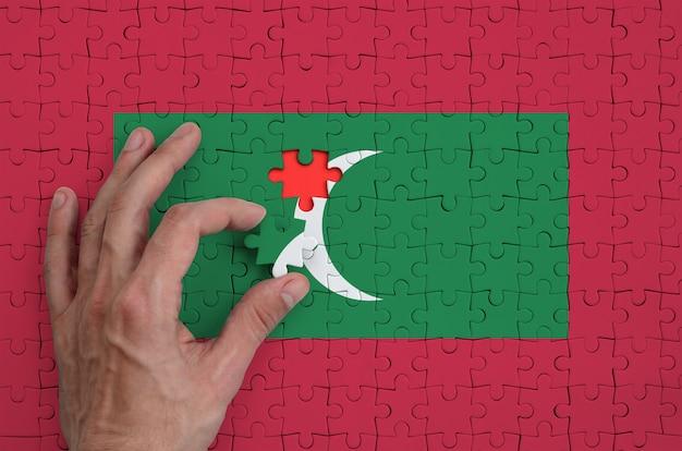 Die flagge der malediven ist auf einem puzzle abgebildet, das mit der hand des mannes gefaltet wird