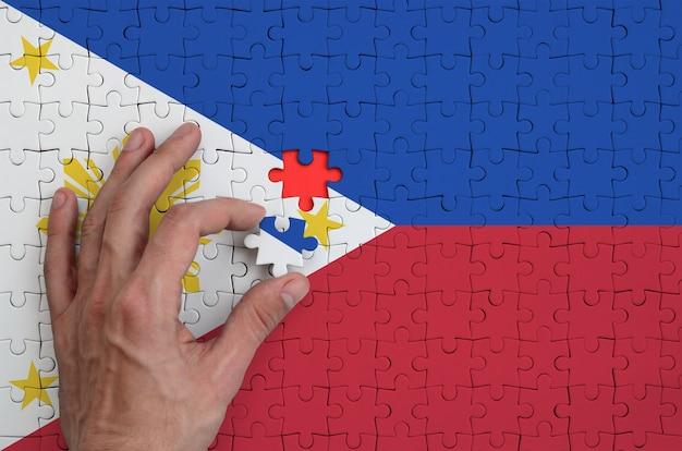 Die flagge der philippinen ist auf einem puzzle abgebildet, das mit der hand des mannes gefaltet wird
