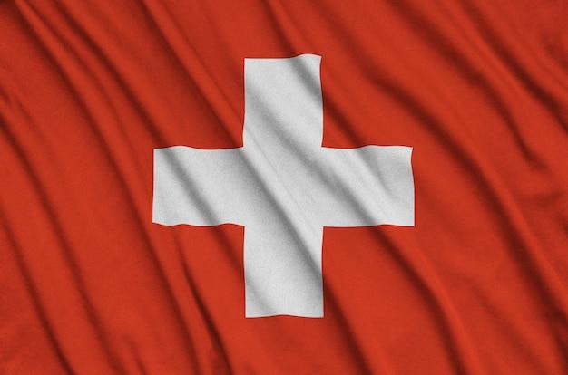 Die flagge der schweiz ist auf einem sportstoff mit vielen falten abgebildet.