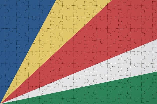 Die flagge der seychellen ist auf einem gefalteten puzzle abgebildet