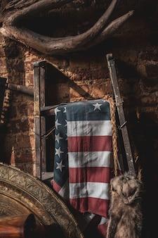 Die flagge der vereinigten staaten hing an einem metallständer auf einem alten dachboden
