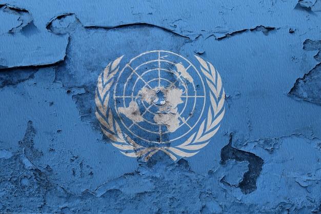 Die flagge der vereinten nationen, die auf schmutz gemalt wurde, knackte wand