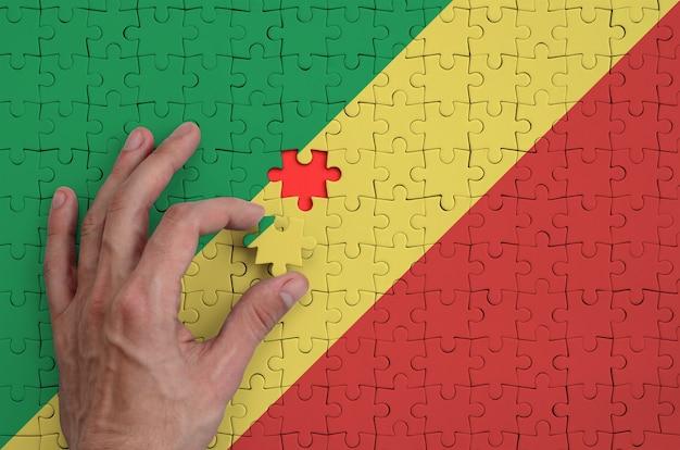 Die flagge des kongo ist auf einem puzzle abgebildet, das der mann mit der hand zu falten versucht
