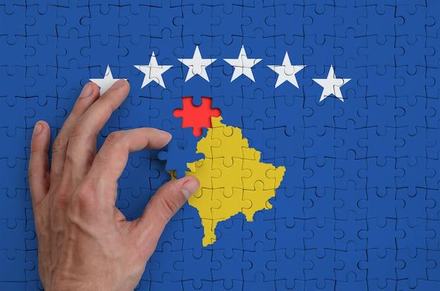 Die flagge des kosovo ist auf einem puzzle abgebildet, das mit der hand des mannes gefaltet wird