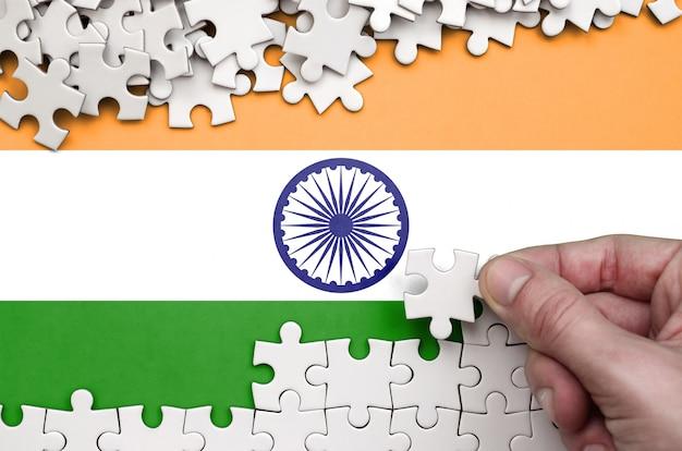 Die flagge indiens ist auf einem tisch abgebildet, auf dem die menschliche hand ein puzzle weißer farbe faltet