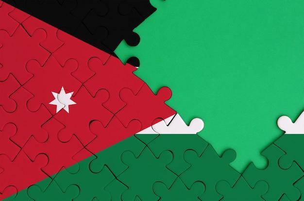 Die flagge jordaniens ist auf einem fertigen puzzle mit freiem grünem platz auf der rechten seite abgebildet