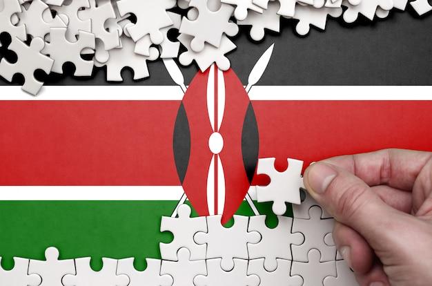Die flagge kenias ist auf einem tisch abgebildet, auf dem die menschliche hand ein puzzle weißer farbe faltet