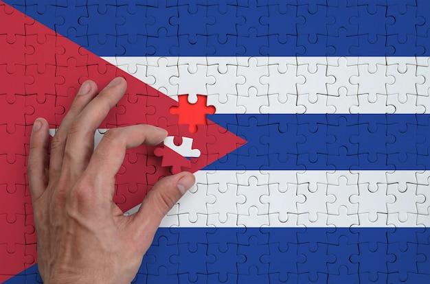 Die flagge kubas ist auf einem puzzle abgebildet, das der mann mit der hand zu falten versucht