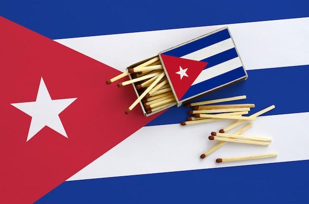 Die flagge kubas ist auf einer offenen streichholzschachtel abgebildet, von der mehrere streichhölzer stammen und auf einer großen flagge liegt