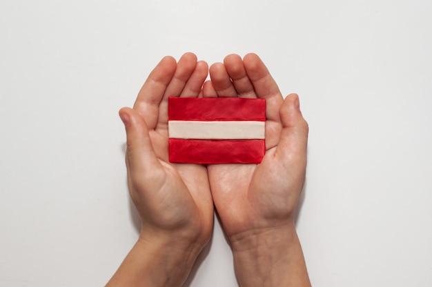 Die flagge lettlands aus plastilin in den händen
