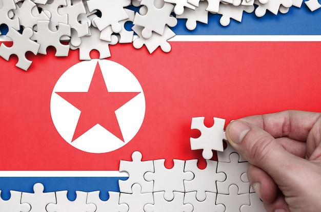 Die flagge nordkoreas ist auf einem tisch abgebildet, auf dem die menschliche hand ein puzzle weißer farbe faltet
