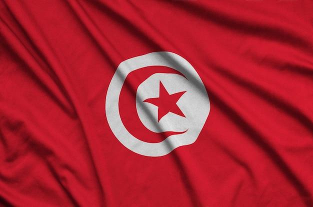 Die flagge tunesiens ist auf einem sportstoff mit vielen falten abgebildet.