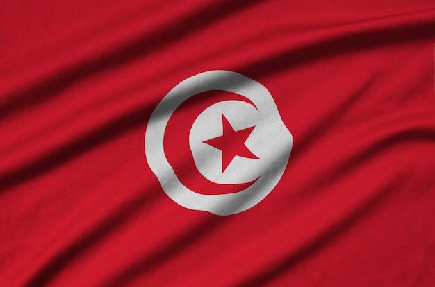 Die flagge tunesiens ist auf einem stoff mit vielen falten abgebildet