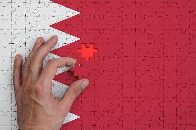Die flagge von bahrain ist auf einem puzzle abgebildet, das mit der hand des mannes gefaltet wird