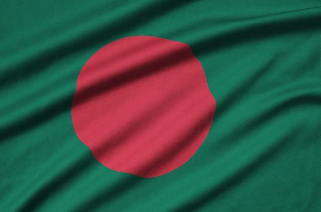 Die flagge von bangladesch ist auf einem sportstoff mit vielen falten abgebildet.