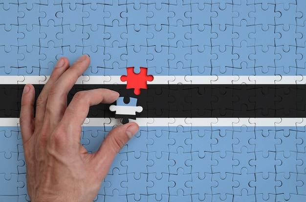 Die flagge von botswana ist auf einem puzzle abgebildet, das der mann mit der hand zu falten versucht