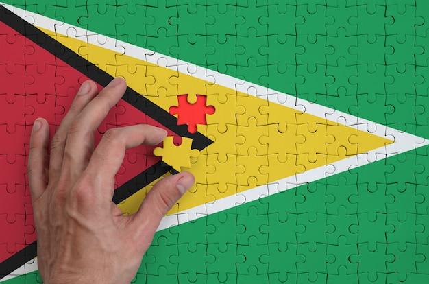 Die flagge von guyana ist auf einem puzzle abgebildet, das mit der hand des mannes gefaltet wird
