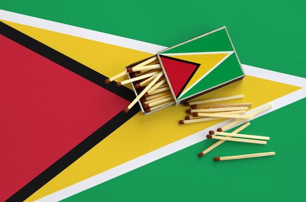 Die flagge von guyana ist auf einer offenen streichholzschachtel abgebildet, von der mehrere streichhölzer stammen und auf einer großen flagge liegt
