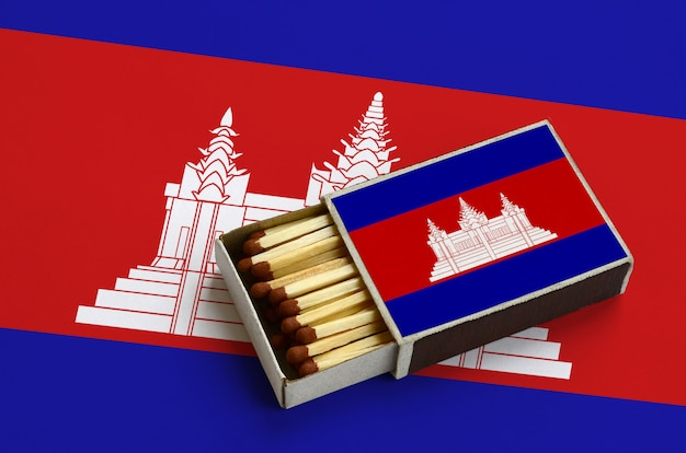 Die flagge von kambodscha wird in einer offenen streichholzschachtel gezeigt, die mit streichhölzern gefüllt ist und auf einer großen flagge liegt