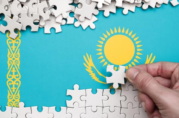Die flagge von kasachstan ist auf einem tisch abgebildet, auf dem die menschliche hand ein puzzle weißer farbe faltet