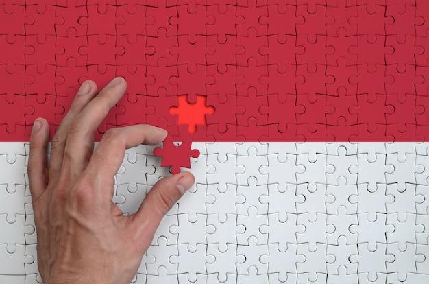 Die flagge von monaco ist auf einem puzzle abgebildet, das mit der hand des mannes gefaltet wird