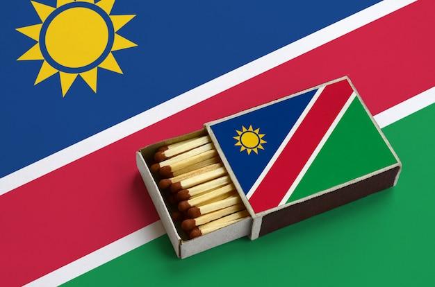 Die flagge von namibia wird in einer offenen streichholzschachtel gezeigt, die mit streichhölzern gefüllt ist und auf einer großen flagge liegt