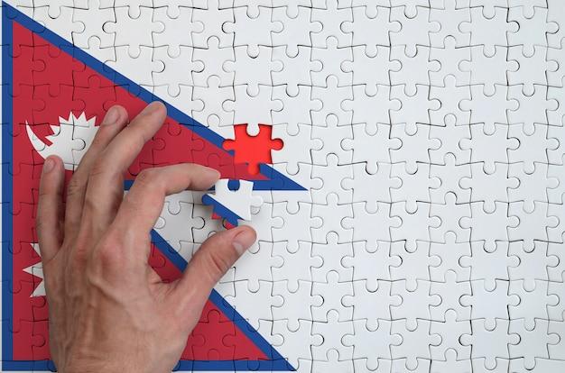Die flagge von nepal ist auf einem puzzle abgebildet, das der mann mit der hand zu falten versucht