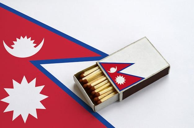 Die flagge von nepal wird in einer offenen streichholzschachtel gezeigt, die mit streichhölzern gefüllt ist und auf einer großen flagge liegt
