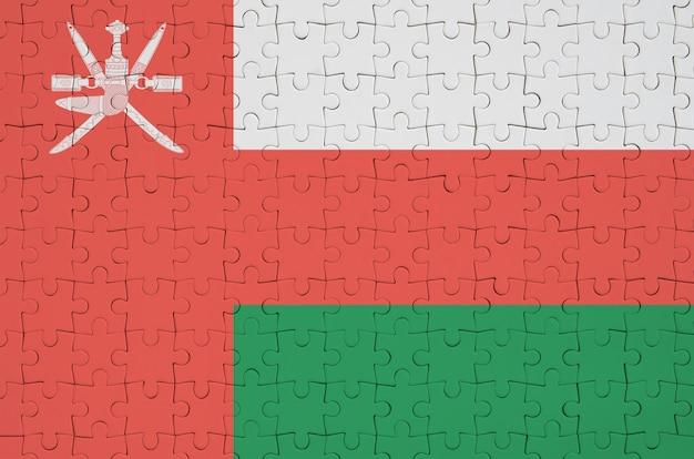 Die flagge von oman ist auf einem gefalteten puzzle abgebildet