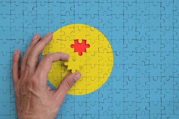 Die flagge von palau ist auf einem puzzle abgebildet, das mit der hand des mannes gefaltet wird