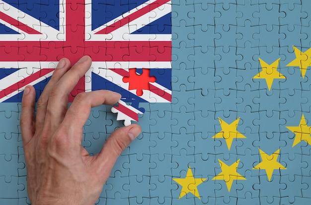 Die flagge von tuvalu ist auf einem puzzle abgebildet, das der mann mit der hand zu falten versucht