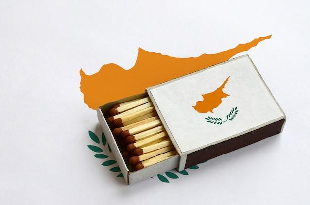 Die flagge zyperns wird in einer offenen streichholzschachtel gezeigt, die mit streichhölzern gefüllt ist und auf einer großen flagge liegt